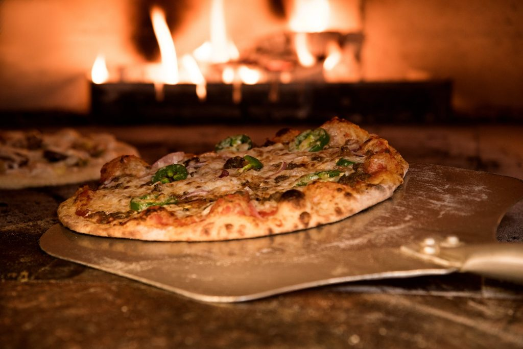 Pizza being cooked in a wood oven